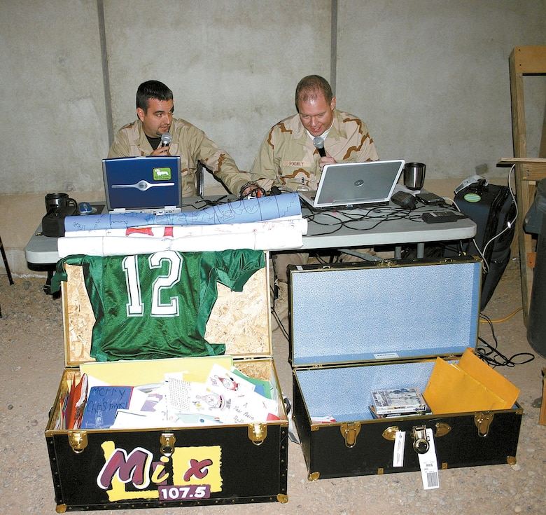 Clovis radio personalities Duffy Moon (left) and Steve Rooney (right) perform their usual morning show live from Balad Air Base, Iraq, outside the recreation center. Deployed Airmen from the 27th Fighter Wing were given the opportunity to send live holiday greetings back home. In front of them are two footlockers they brought with them containing messages, CDs, DVDs and phone cards donated by members of the local communities. (photo by Staff Sgt. Craig Seals)