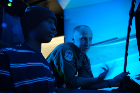 """TYNDALL AIR FORCE BASE, Fla. --  David Baptiste, the 95th Fighter Squadron's """"Pilot for the Day,"""" operates an F-15 flight simulator with the help of Capt. Dave Christensen, 95th FS instructor pilot, Nov. 21. (U.S. Air Force photo by Tech. Sgt. Edward Gyokeres)"""