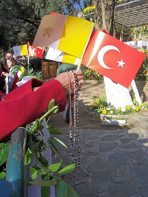 An attendee waits to celebrate mass with Pope Benedict XVI in Ephesus, Turkey, Nov. 29, holding the Catholic Flag, the Turkish flag and a number of rosaries.  (Courtesy photo)