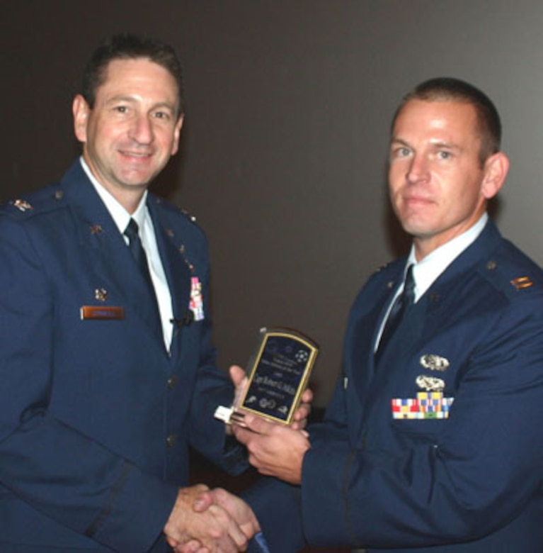 Col. Mark Correll, 72nd Air Base Wing commander, presents the Tinker Air Force Base Athlete of the Year trophy to Capt. Robert Atkins.