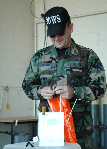 Staff Sgt. Brad Snyder, 30th Weather Squadron, attaches a parachute to the radiosonde which is then attached to a weather balloon at the balloon facility on Vandenberg.  The balloons travel to a height of more than 110,000 feet before exploding and sending the attached global positioning system gliding back to earth via the small parachute.  (U.S. Air Force photo by Staff Sgt. Raymond Hoy)