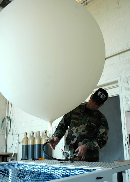 Staff Sgt. Brad Snyder, 30th Weather Squadron, fills a weather balloon with helium at the balloon facility on Vandenberg.  The balloons travel to a height of more than 110,000 feet before exploding and sending the attached global positioning system gliding back to earth via a small parachute.  (U.S. Air Force photo by Staff Sgt. Raymond Hoy)