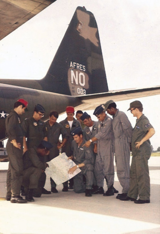 Air crews gather beneath the tail of one of the 926th Tactical Airlift Group's C-130s in the early 1970s.