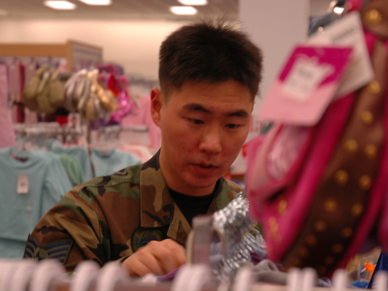 BUCKLEY AIR FORCE BASE, Colo. -- Staff Sgt. Hyun Yang, 460th Civil Engineer Squadron, shops for clothes as part of a shopping spree for the Angel Tree at the Buckley Exchange Dec. 6. Team Buckley first sergeants and other volunteers spent approximately $4,600 donated by the Homefront Heroes Denver chapter, a non-profit military support group. The Angel Tree project provides family members of all services', E-5's and below, gifts for the holidays. (U.S. Air Force photo by Staff Sgt. Sanjay Allen)