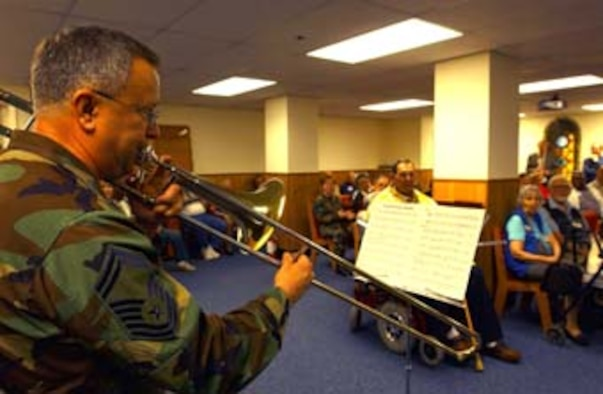 WASHINGTON, D.C. -- Senior Master Sgt. Ray Price, 459th Maintenance Squadron propulsion superintendent, plays slide trombone for Armed Forces Retirement Center residents Nov. 16. Sergeant Price played each service branch's anthem for the residents. (U.S. Air Force photo by Staff Sgt. Amaani Lyle)