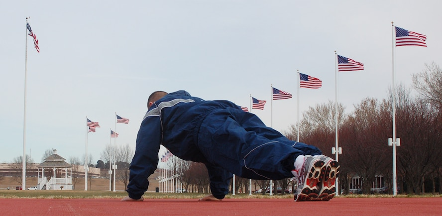 An Airman works out on the new exercise pad located at the south corner of the parade ground. The new pad, similar to the running surface in the Offutt Field House, is softer, drier and more forgiving than the concrete or grass that Team Offutt members had to use before it was built late this summer. (Air Force photo by 1st Lt. John Severns)
