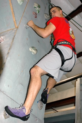 """Brody Johnson climbs """"The Tower"""" at the Outdoor Recreation Indoor Climbing Wall. The Tower features a large overhang with few holds on the wall to provide a challenging climb. The climbing wall is open every day and is free for active duty. However, climbers must bring their own belayers. Belayers are the people on the other end of the rope who control the falling climber so they do not fall very far. (U.S. Air Force photo by Jennifer Brugman/60th Air Mobility Wing Public Affairs)"""