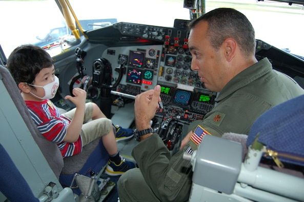 Maj. Jerry Malloy shows 5-year-old Natsuki Takeda the cockpit of a KC-135 Stratotanker Dec. 5 at Andersen Air Force Base, Guam. Andersen AFB members teamed up with the Make-A-Wish Foundation of Guam to grant Natsuki's wish of seeing a military aircraft. Major Maloy is a a KC-135 instructor pilot with the 506th Expeditionary Air Refueling Squadron. (U.S. Air Force photo/Master Sgt. Ann Bennett)