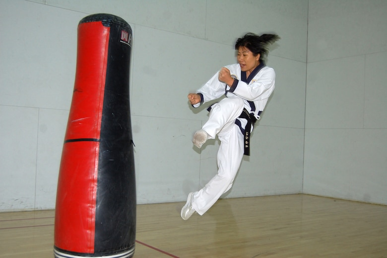 Kumye Moore demonstrates a Tae Kwon Do jumping side kick at one of her classess at the Rosburg Fitness Center on Dec. 4, 2006. Ms. Moore is a fourth Dan black belt instructor with the World Tae Kwon Do Federation. (Photo by Airman 1st Class Julius Delos Reyes)