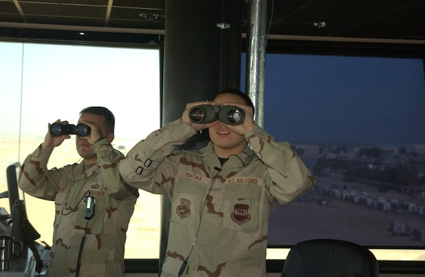 BALAD AIR BASE, Iraq -- Senior Airman Joshua Matias (right), 332nd Expeditionary Operations Support Squadron air traffic control apprentice, scans the Balad Air Base flightline Tuesday. Airman Matias was recognized with the 2006 Air Traffic Control Association Lingiam Odems Memorial Award. (U.S. Air Force photo by Senior Airman Josh Moshier)