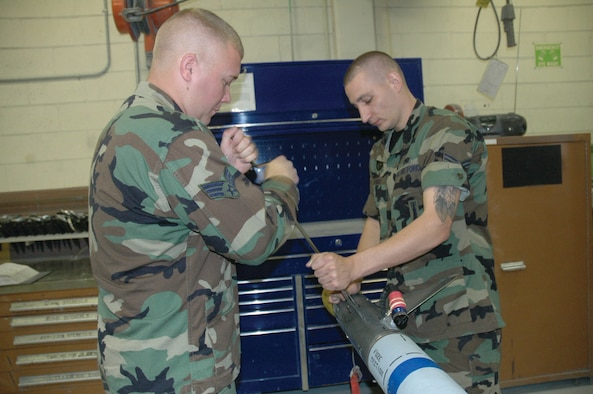 TYNDALL AIR FORCE BASE, Fla. --  Senior Airmen Christopher Bratcher (left) and Jeffrey Hird, both precision guided munitions shop crew members, remove the fins from the guidance control section of a captive air training missile (CATM-9) prior to performing maintenance. (U.S. Air Force photo by Staff Sgt. Stacey Haga)