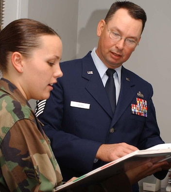 Airman 1st Class Sara Johnson, left, 81st Training Wing administrative staff, goes over inprocessing paperwork with Chief Master Sgt. Ronald Owens, the wing's new command chief. He replaces Chief Master Sgt. Aliquippa Allen, who retired. He comes to Keesler from Charleston Air Force Base, S.C., where he was the 437th Mission Support Group's superintendent. He's served in squadron to major command positions and was deployed to Iraq as chief enlisted manager of the 447th Air Expeditionary Group at Baghdad International Airport. (U.S. Air Force photo by Kemberly Groue)