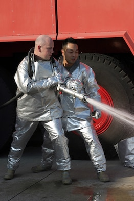 Staff Sgt. Christopher Hill learns a different technique for extinguishing fires from Japan Air Self Defense Force Master Sgt. Masashi Mitake at Tsuiki Air Base, Japan. Six Kadena Air Base, Japan, NCOs took part in a bilateral exchange from Dec. 5 to 13 at a remote seaside JASDF base. The NCOs lived and worked alongside JASDF Airmen in similar jobs to build relations and promote interoperability. Sergeant Hill is with the 18th Civil Engineer Squadron, (U.S. Air Force photo/Master Sgt. Jeffery Loftin)