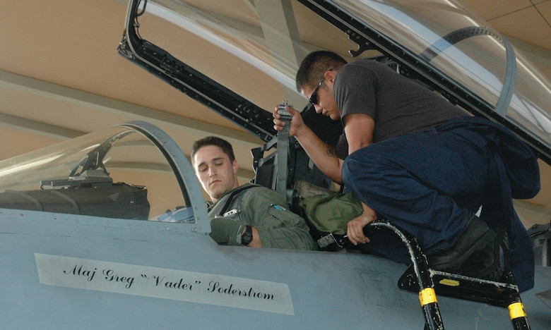 TYNDALL AIR FORCE BASE, Fla. --  Airman 1st Class Jesus Ortiz, 2nd Aircraft Maintenance Unit crew chief, right, assists Lieutenant Bursi as the pilot straps into the cockpit during one of his initial F-15 sorties here. (U.S. Air Force photo by 1st Lt. Amanda Ferrell)