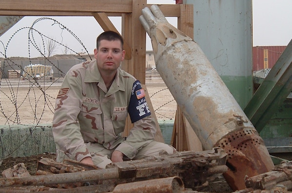 """TALLIL AIR BASE --  Staff Sgt. Edward Gyokeres poses for a picture atop discarded aircraft cannons. Sergeant Gyokeres wrote a journal called """"The Tallil Chronicles,"""" and has been published several times. (U.S. Air Force photo by Airman 1st Class Chad Christiansen)"""