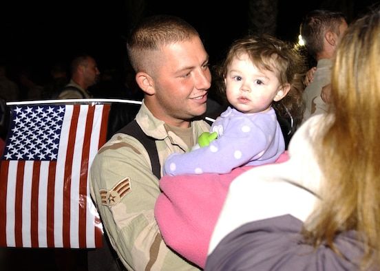 Senior Airman Ryan Phillips, 30th Civil Engineer Squadron,  reunites with his loved ones after landing on the Vandenberg flightline on December 7, 2006. Airman Phillips was one of 39 CE troops to return from deployment in support of the Global War on Terror. (U.S. Air Force photo by Airman 1st Class Christopher Hubenthal)