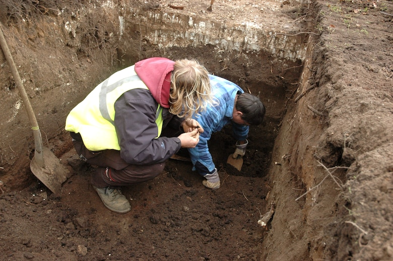 British archeologist Nick Taylor (left) inspects fragments of rock from a dig site as fellow archeologist Jonathan Van Jennians continues to dig. The trial trenches are being dug at RAF Mildenhall, England where new officer housing units are to be built. The United Kingdom requires all construction projects go through this dig to ensure no  potential historical artifacts are destoyed. (U.S. Air Force photo/Tech. Sgt. Scott Wakefield)