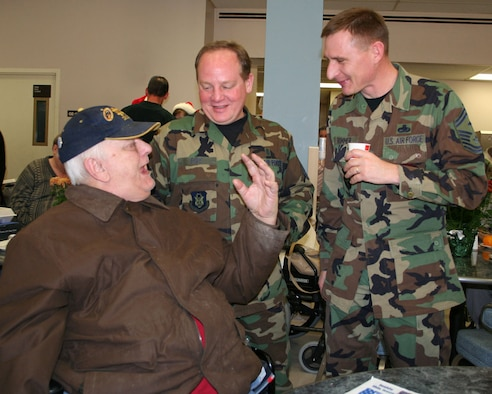 DAYTON, Ohio -- Veteran Walter Shelhorn talks to Master Sgt. Jim Foy (center) and Senior Master Sgt. Mike Brimmer (Left) during a visit at the Dayton Veterans Administration Nursing Home during their annual holiday party. (U.S. Air Force photo/Maj. Jose Cardenas).