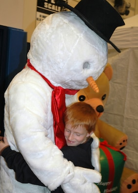 SCHRIEVER AIR FORCE BASE, Colo. -- James, age 9, hugs Frosty the Snowman during the Children's Holiday Festival at the Main Fitness Center here Saturday. Nearly 500 children attended this year's festival. (U.S. Air Force photo/Senior Airman Amanda Delisle)