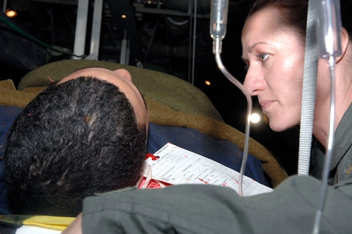 """Lt. Dinah Lewis reassures Airman 1st Class Justin Vargas, a """"burn victim"""" being airlifted during the Collaborative Multi-Agency Medical Exercise, known as CMAX, that took place in the Washington D.C. area on Dec. 7.  The annual exercise was designed to test the capabilities of the local authorities to handle a major catastrophe. This was the first year that patient transport was included in the exercise.  Lieutenant Lewis is a nurse from the Delaware Air National Guard and Airman Vargas is with the 79th Medical Support Squadron, Bolling Air Force Base, D.C.  (U.S. Air Force photo/Tech. Sgt. Cohen Young)"""