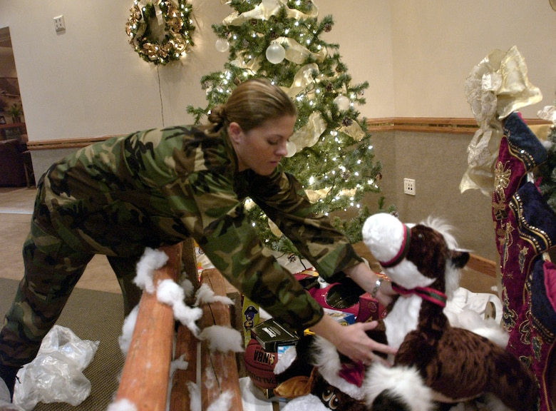 Captain Jessica Martin, acting chief of Community Relations, Nellis Air Force Base, Nev., Office of Public Affairs Office, places a toy under the Christmas tree at the Officers' Club Dec. 12. The toys were donated by the Civilian Military Council and will be given to deserving children by the base's Operation Warm Heart Adopt-A-Family program. (U.S. Air Force Photo/Senior Airman Larry E. Reid Jr.)