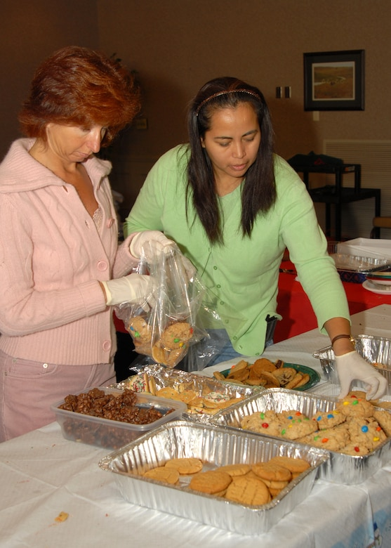 Lorianne Powers, wife of Lt. Col. John Powers, and Gina Lockard, wife of Col. Scott Lockard, sort donated cookies for dorm residents as part of Operation Cookie Drop Wednesday. The operation helps spread holiday cheer by providing Airmen in the dorms with a taste of home for the holidays. Photo by Airman Vanessa Dale