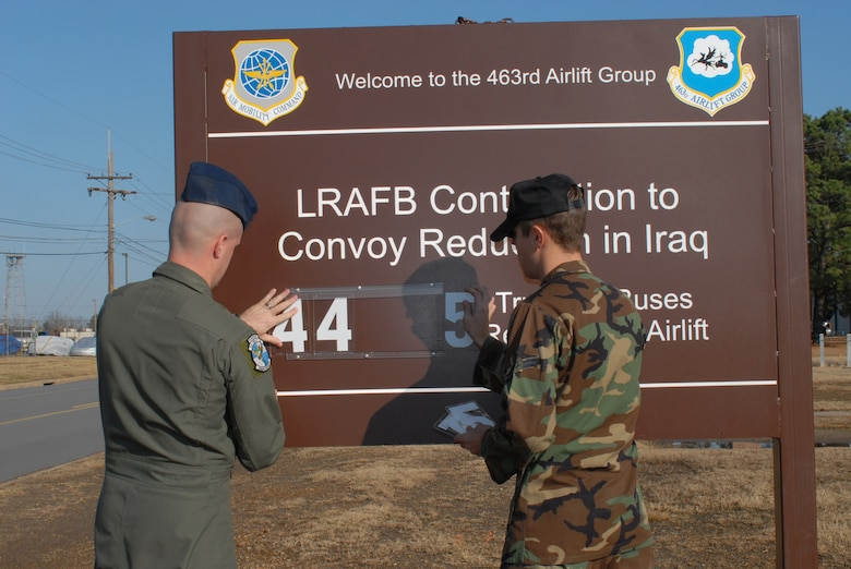 Senior Airman Stephen Bryant (left), a 61st Airlift Squadron loadmaster, and Airman 1st Class Denton Lester, a 463rd Aircraft Maintenance Squadron crew chief, update the numbers on the LRAFB Contribution to Convoy Reduction in Iraq sign Dec. 12 to 4,455 trucks and buses reduced by airlift. The sign outiside the 463rd Airlift Group headquarters building tracks the number of trucks and buses by airlifting people and equipment instead of dangerous convoy missions.
