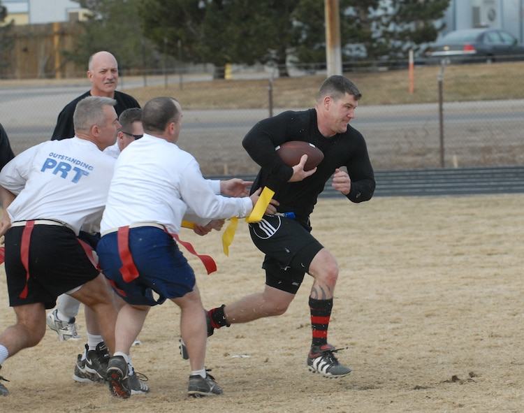 Jeff Beckford, Eagles/Commanders team member, breaks through the Chiefs/Shirts defense in a flag football game Dec. 14. The Chiefs slaughtered the Eagles, 31-0. (U.S. Air Force photo by Airman 1st Class Alex Gochnour)