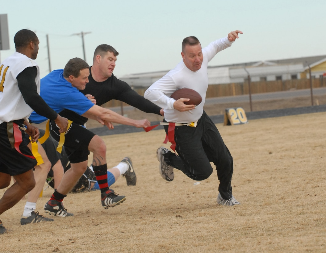 Chief player Kevin Candler tries to squeeze by Eagle members Jeff Beckford and David Ziegler during a flag football game between Buckley chiefs and first sergeants against Buckley colonels and commanders Dec. 14. The Chiefs/Shirts won 31-0. (U.S. Air Force photo by Airman 1st Class Alex Gochnour)