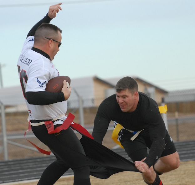 Eagles/Commanders team member Jeff Beckford rips Chiefs/Shirts Randall Raper's shorts off during a flag football game Dec. 14 that was put on to raise canned goods for Operation Warmheart and give base enlisted and officer leadership a chance for friendly competition. The Chiefs/Shirts shut the Eagles/Commanders out 31-0. (U.S. Air Force photo by Airman 1st Class Alex Gochnour)