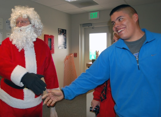 Santa, or Deacon Richard Borda from the 460th Space Wing Chapel, delivers cookies to Staff Sgt Martin Campos, from the 460th Security Forces Squadron K-9 unit, and his colleagues Dec. 14 as part of the chapel's annual Cookie Caper drive. The chapel collected close to 10,000 cookies to deliver to every Buckley unit.