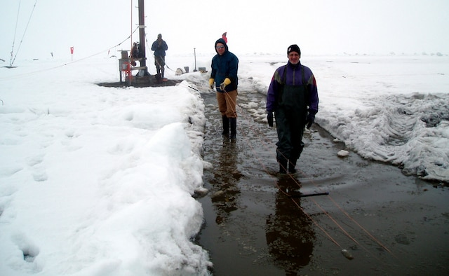 2nd Lt. Isseyas Mengistu (background), 1st Lt. Robert Esposito (middle) and Jake Quinn, researchers serving with Air Force Research Laboratory's Space Vehicles Directorate, lay out the ionosonde antenna elements on the frozen tundra of Greenland prior to hoisting them up an 82-foot pole.  (Air Force photo)