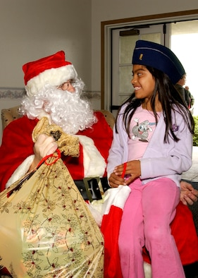 Santa Clause gives 7-year-old Violeta Guia her bag of Christmas goodies at Vandenberg's Pacific Coast Club during Operation Kids Christmas December 9, 2006.   OKC provided more than 200 underpriveledged children Christmas presents and a holiday dinner gift certificate.  The event is made possible through multiple fundraising events and corporate sponsors.  This was the 47th annual OKC at Vandenberg.  (U.S. Air Force photo by Airman Stephanie Longoria)