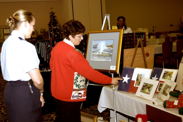 Charlotte Nelms of San Antonio, Texas, tells Maj. Rebecca Lehr, 59th Training Squadron, how a squadron coin fits perfectly in the middle of the star. Ms. Nelms was one of more than 20 vendors at the annual Christmas Craftsfest on Lackland Air Force Base, Texas, Dec. 15.  (USAF photo by April Blumer)