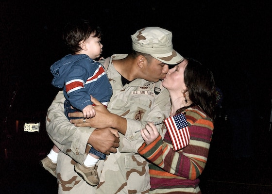 "While holding his 13-month-old son, Gabriel, Staff Sgt. Matthew Rodriguez, 37th Security Forces Squadron, receives a loving ""welcome home"" kiss from his wife, Polly Rodriguez. Sergeant Rodriguez returned home from a six-month deployment Sunday evening with more than 110 other Airmen from across the Air Force. (Photo by Alan Boedeker)"