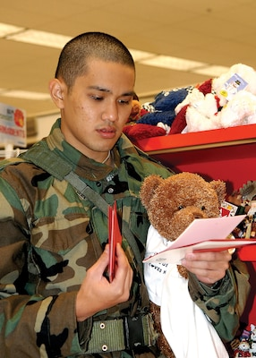 Trainee Ryan Kanasusuku, 324th Training Squadron, selects cards and gifts at the Main Exchange on Lackland Air Force Base during the Shop-A-Trainee program Dec. 9.