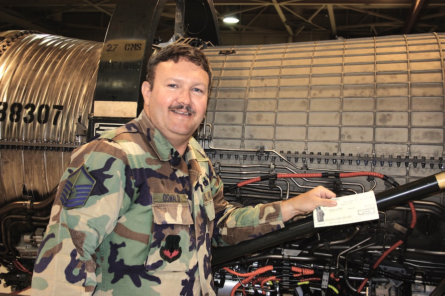 Master Sgt. Ken Oswald, 27th Fighter Wing Safety, Cannon Air Force Base, N.M., displays a check as he stands in from on an F-16 compressor case. Sergeant Oswald received $7,000 on May 4 for improving the procedure for removing the compressor's blade lock, a procedure that prevents future damage and result in saving the Air Force $50,342. He will represent Air Combat Command for the 2006 Air Force Exceptional Innovator Award. (Air Force photo by Greg Allen)