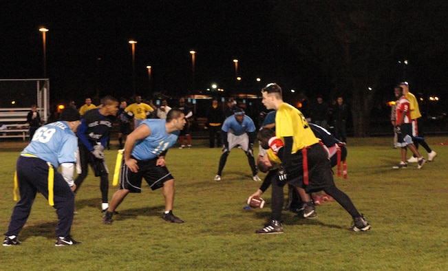 The 60th Security Forces Squadron (gold) gets set to run a play against the 60th Operations Support Squadron (blue) during the flag football season championship, Dec. 6. The 60th SFS, using aggressive defense, was able to narrowly defeat the 60th OSS by a score of 7 to 6. (U.S. Air Force photo by Staff Sgt. Candy Knight)