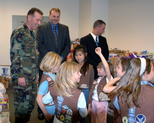 Col. Steve Arquiette, (left), 60th Air Mobility Wing commander, speaks with members of Girl Scout Troop 96 during the Team Travis Food Drive Dec. 6. Team Travis members donated approximately 5,000 pounds of food during the Air Force Office of Special Investigations, Detachment 303-sponsored food drive. In conjunction with local Girl Scouts, the food was delivered to the Vacaville Storehouse Dec. 9.