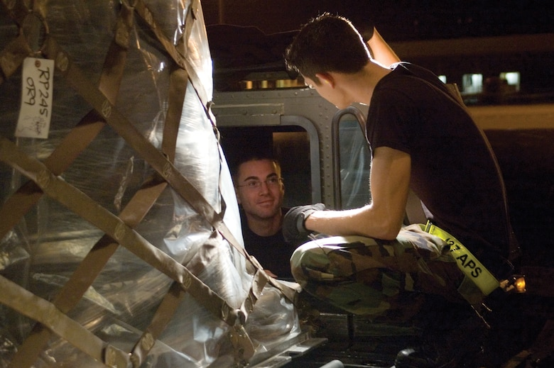 Airman 1st Class Russell Berry (left) and Airman 1st Class Johnathan Lemond, 437th Aerial Port Squadron air transportation specialists, discuss aircraft loading procedures while loading a Boeing 747 on the flightline in the early morning hours Dec. 13. (U.S. Air Force photo/Airman 1st Class Sam Hymas)