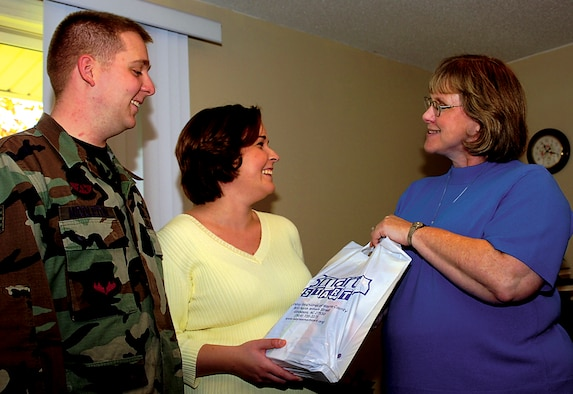 SEYMOUR JOHNSON AIR FORCE BASE, N.C. - Staff Sgt. Corey Middleton, 4th Equipment Maintenance Squadron, and his wife receive an information gift bag from Marcia Sampson, 4th Fighter Wing life skills outreach nurse, as part of the Born Learning Program, which provides information to parents on educating newborn children. (U.S. Air Force photo by Airman 1st Class Greg Biondo)