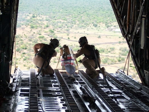 Staff Sgt. Patrick Delselva (left) and Senior Airman Chris Elder roll a miniature pallet of candy off the cargo ramp of a C-130 Hercules Dec. 14 to children in the Dadaab region of northeastern Kenya. In a six-day span the Air Force delivered more than 211,000 pounds of supplies to the region in support of Operation Unity Knight. Both Airmen are deployed to the 746th Expeditionary Airlift Wing in Southwest Asia from Dyess Air Force Base, Texas. (U.S. Air Force photo/Tech. Sgt. Steve Staedler)