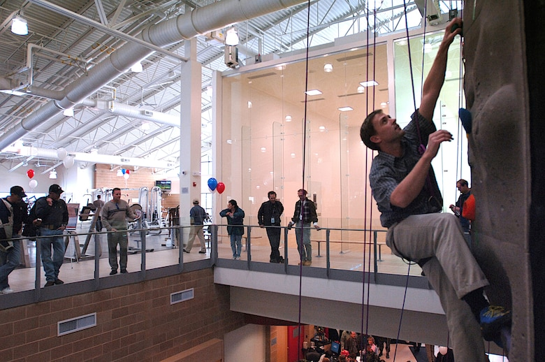 A climber tries out the new indoor rock climbing wall during Monday's grand opening ceremony for Hill's new state-of-the-art fitness center.