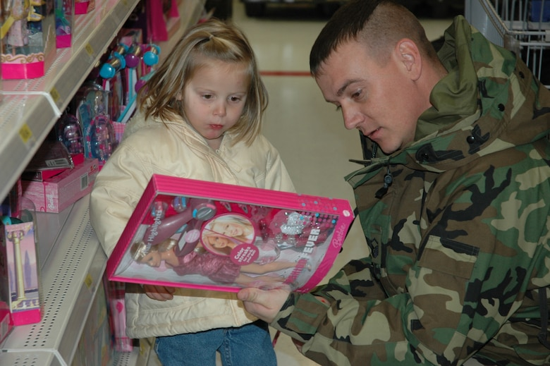 Master Sgt. Ernest Jepperson helps Madison choose a Barbie for a Christmas present.