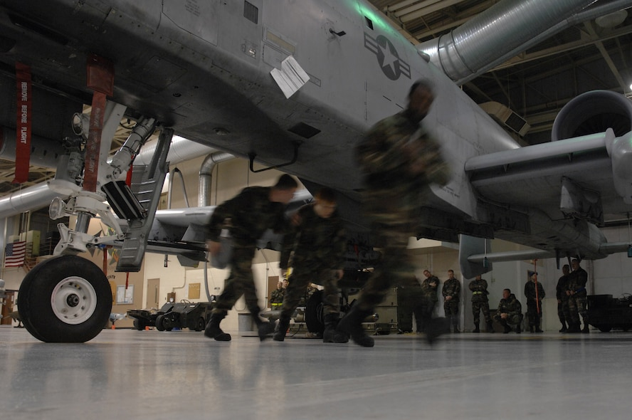EIELSON AIR FORCE BASE, Alaska -- The team of Staff Sgt Michael Woroniecki (left), Senior Airman Vankeithin Simmons (right), and Joshua Gess (middle) move quickly under an A-10 Thunderbolt II to complete their portion of the Load Crew of the Quarter contest here on 15 December. The Airmen represent the 355th Aircraft Maintenance Unit (AMU) and the quarterly contest pitts the 18th AMU versus the 355th AMU. Both teams loaded 2 MK-82 low drag bombs and one AIM-9 sidewinder missile to their respective aircraft. (U.S. Air Force Photo by Staff Sgt Joshua Strang)