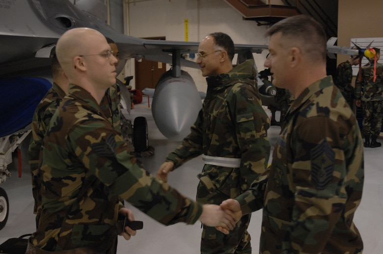 EIELSON AIR FORCE BASE, Alaska -- Brig. Gen. David Scott (middle), Commander, 354 Fighter Wing, and Chief Master Sgt. Stephen Ludwig, Command Chief, 354th Fighter Wing, congratulate the team of Staff Sgt Aaron Slay (front left), Senior Airman Michael Lee and Senior Airman Corneilius Cutler for a job well done after their timed run during the Load Crew of the Quarter contest here on 15 December. The Airmen represent the 18th Aircraft Maintenance Unit (AMU) and the quarterly contest pitts the 18th AMU versus the 355th AMU. Both teams loaded 2 MK-82 low drag bombs and one AIM-9 sidewinder missile to their respective aircraft.