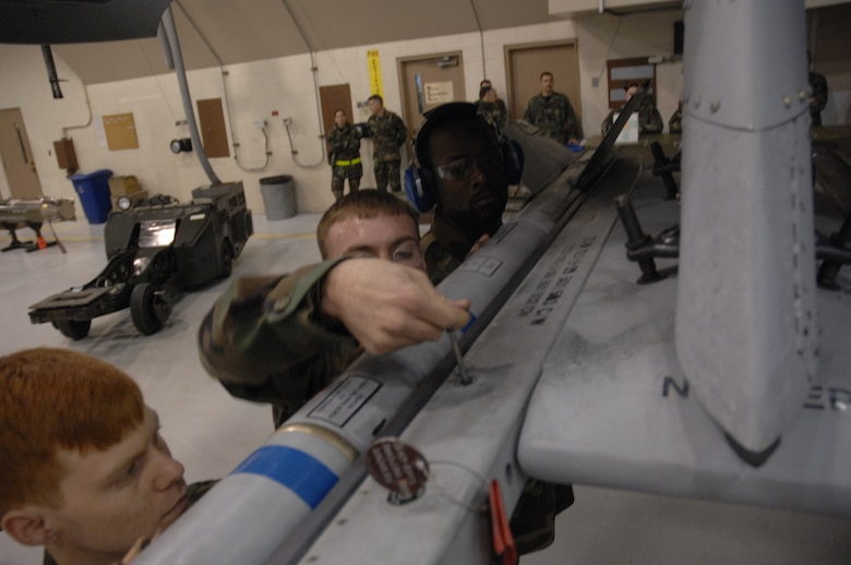 EIELSON AIR FORCE BASE, Alaska -- The team of Staff Sgt Michael Woroniecki (middle), Senior Airman Vankeithin Simmons (right), and Joshua Gess (left) attach a AIM-9 missile to an A-10 Thunderbolt II during the Load Crew of the Quarter contest here on 15 December. The Airmen represent the 355th Aircraft Maintenance Unit (AMU) and the quarterly contest pitts the 18th AMU versus the 355th AMU. Both teams loaded 2 MK-82 low drag bombs and one AIM-9 sidewinder missile to their respective aircraft.