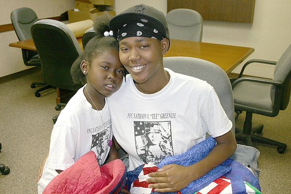 """CANNON AIR FORCE BASE, N.M. -- JaKeria and her mother, Keri Williams, hold the quilts made for their family by Operation Homefront Quilters at Cannon. The quilters made seven quilts for the Williams famly in honor of Army Private First Class Satieon """"Tee"""" Greenlee, Keri's brother, who was killed in Iraq in October. Her husband is Senior Airman Andrew Williams, 27th Component Maintenance Squadron, and Operation IRAQI FREEDOM veteran."""
