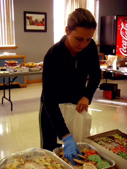 Mrs. Claudia Schnoor, cookie drive volunteer, filled decorated bags with homemade cookies as a special way to show the Airmen living in the dorms that their Air Force family is thinking of them during the holiday season. (U.S. Air Force photo by Airman 1st Class Heather Stanton)