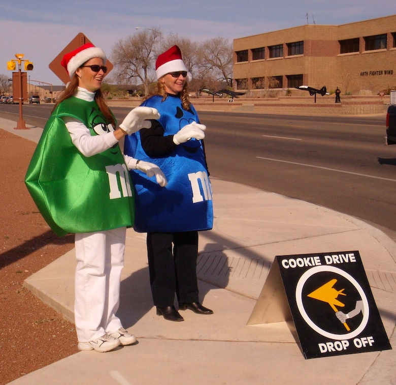 Mrs. Janice Smith and Mrs. Becky McVay, Holloman Officers' Spouses Club members, advertise for the Airmen's Cookie Drive in M&M costumes at the corner of First Street and Arizona Avenue. The drive recieved more than 6,300 cookies for Airmen living in the dorms. (U.S. Air Force photo by Airman 1st Class Heather Stanton)